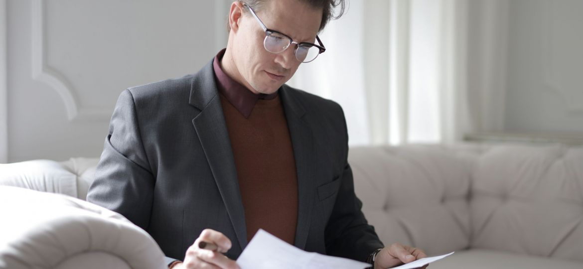 classy-executive-male-reading-papers-on-couch-3760514